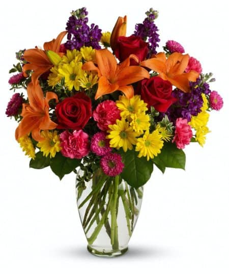 spectacular blend of red roses, orange lilies, purple stock, pink asters and more in a classic clear glass vase